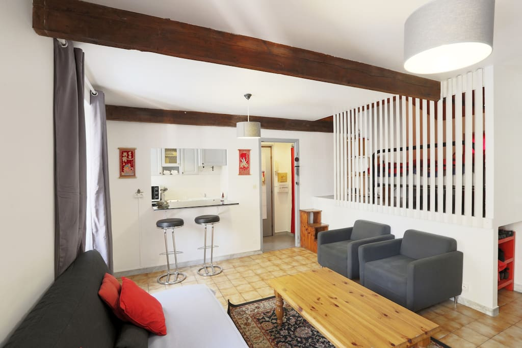 Living room, behind the armchairs and the partitions is the bedroom on the mezzanine (platform)