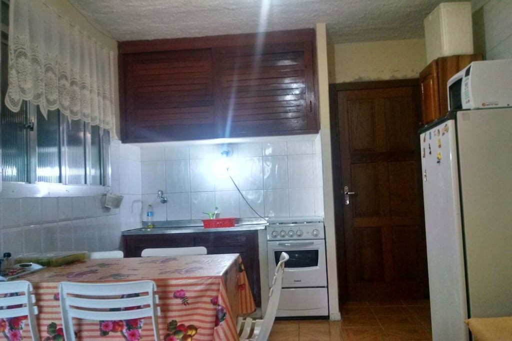 Cozinha com geladeira, fogão, microondas e louça para uso