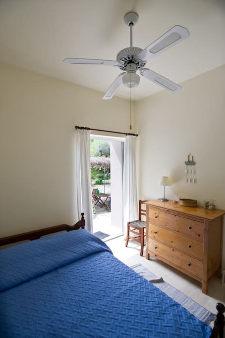 Main bedroom with double bed and access to the yard. There is also a roof fan