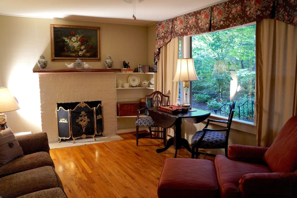 Open plan living room with gas log fireplace, private garden view