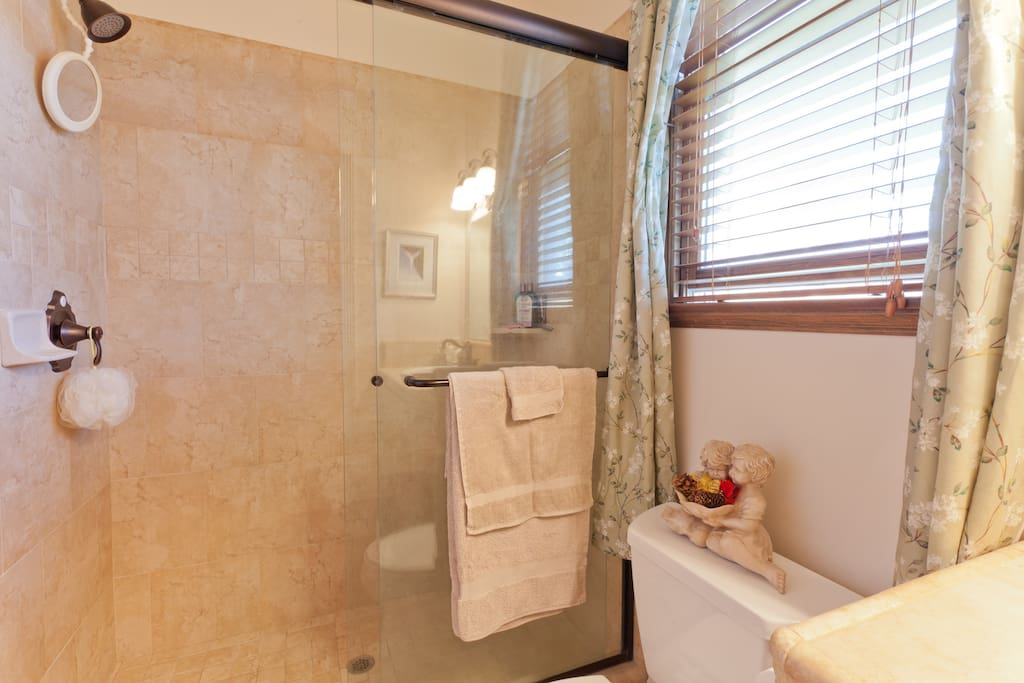Large tile shower, fresh linens, soap and shampoo.