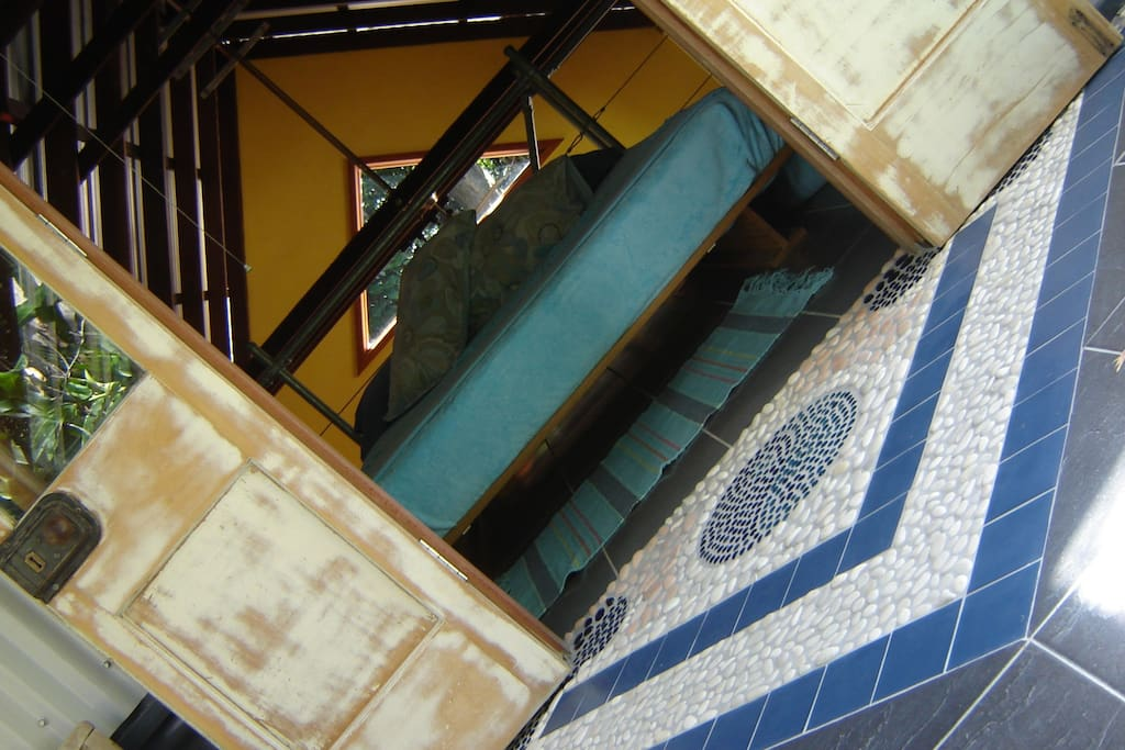 The second bedroom in the loft opens out to a large verandah up in the trees, with handmade mosaics on the floor