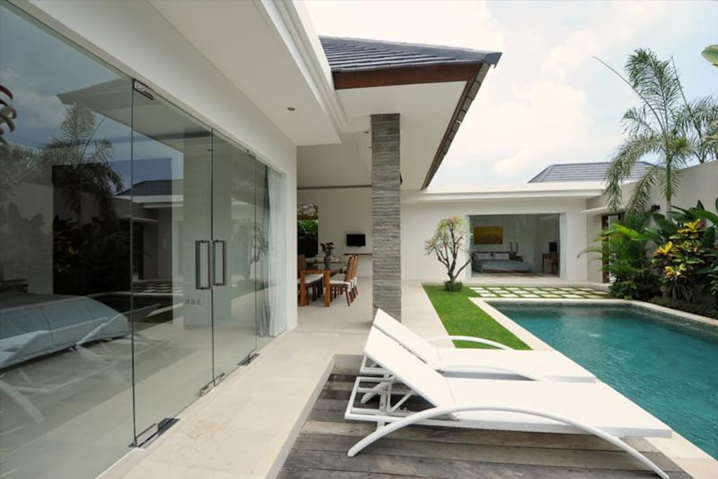 Glass doors of bedroom offering the pool view. In the background, find the other bedroom.