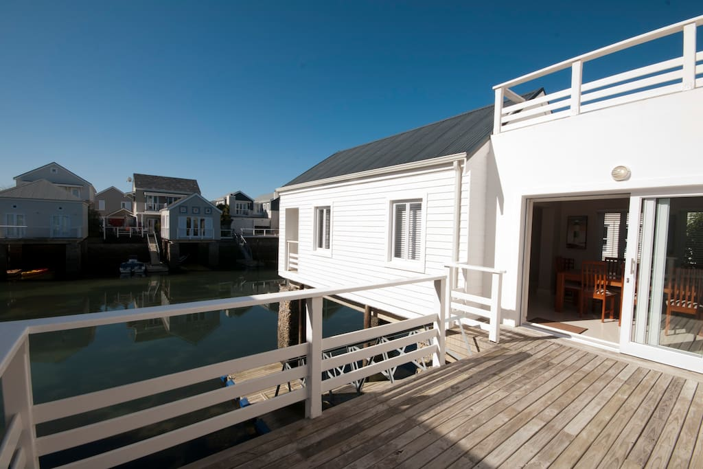 Deck with sun loungers, leading to the canal. Canoe for guest use.