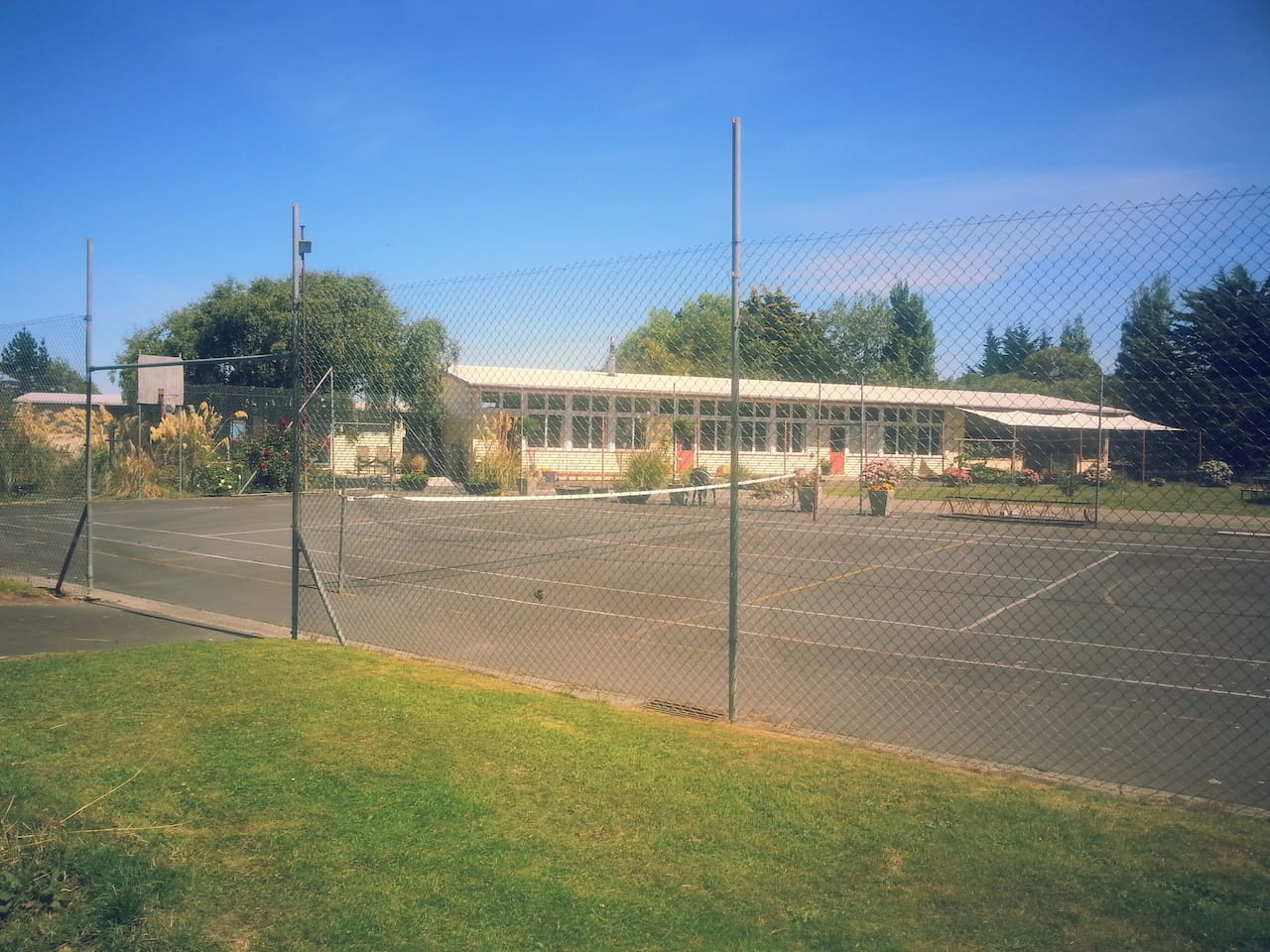 View from the back paddock across the tennis court to the school.  The apartment is behind the left hand birch tree and is very private.
