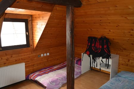 Our warm and comfortable 4 bedroom apartment with exposed wood has a true country side view! It fits two persons in a room and is located just 10km W from Maribor. Small shop and bar nextdoor. Bus stop next to the house.  Animals friendly house:)