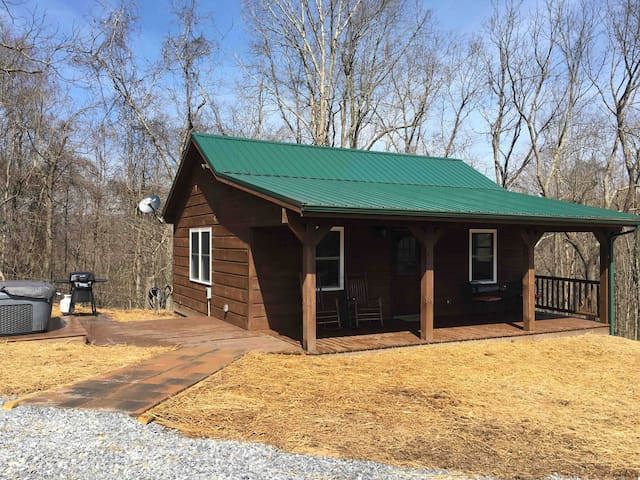 Brand new cabin.  Trying to grow grass, please excuse the hay.    Hot tub, grill, eat or relax on the front porch.