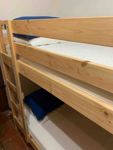 The downstairs bedroom includes two bunk beds, a total of 4 twin beds.
