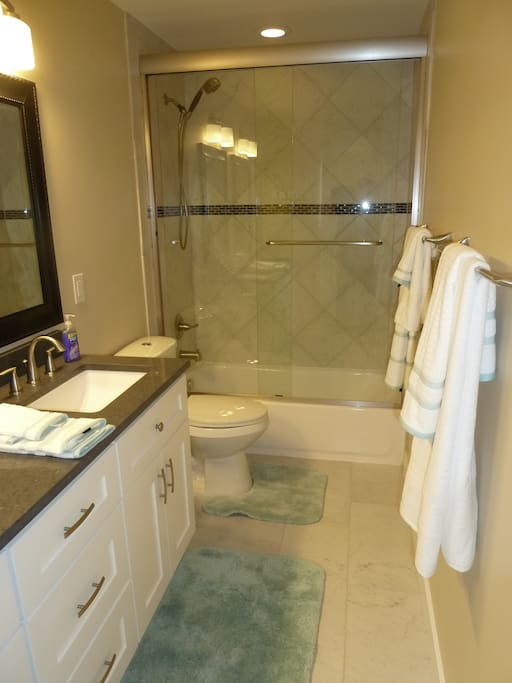 Private bath with 2 sinks, ceramic tile floor, glass shower doors