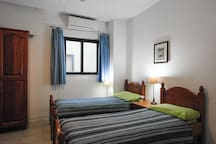 Airconditioned 3rd bedroom with two single beds & 1.2m sofa bed.