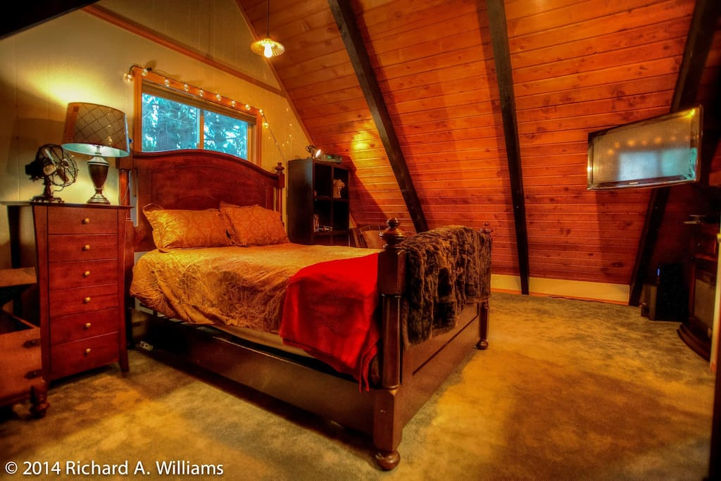 Upstairs loft bedroom with queen bed and electric fireplace and TV
