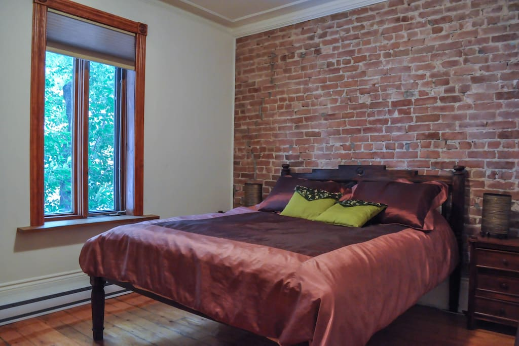 Large front bedroom with brick wall