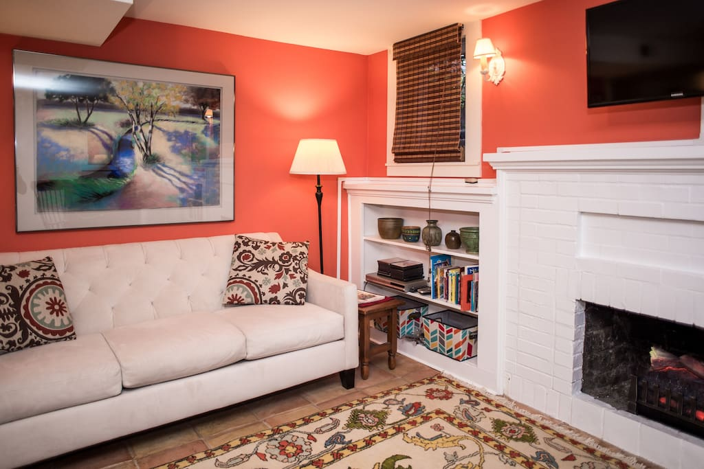 Cozy sitting area with TV books and wifi. Electric fireplace creates a rosy glow.
