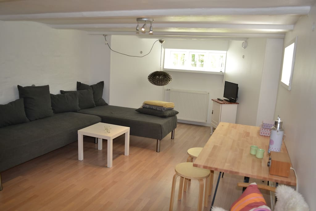 Living room with dining table. The sofa also serves as two beds. For the big family there is a mattress on the floor.