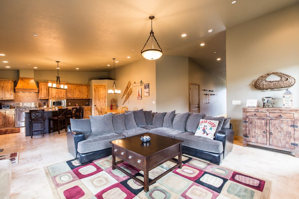 "The living / family room features a large and plush L-shaped couch, river rock fireplace and a 55"" HDTV. This home is a fantastic place for anyone vis"