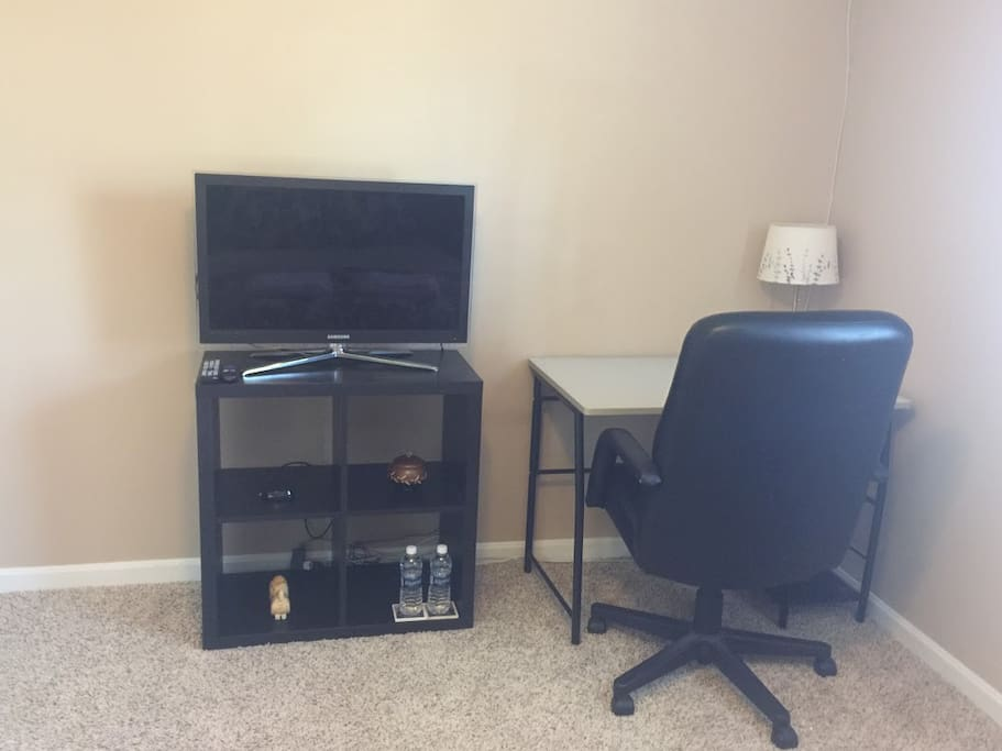 Bedroom is furnished with a flat screen TV equipped with cable channels and a desk