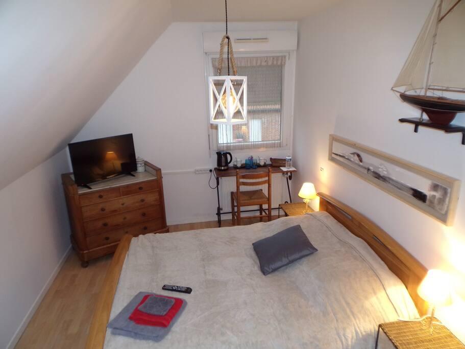 Grand lit confortable , petit bureau et plateau d'accueil