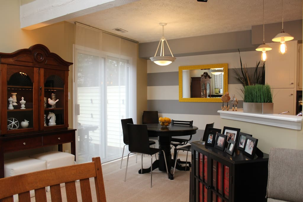 Dining room with adjacent patio. Patio has a gas grill and patio table.