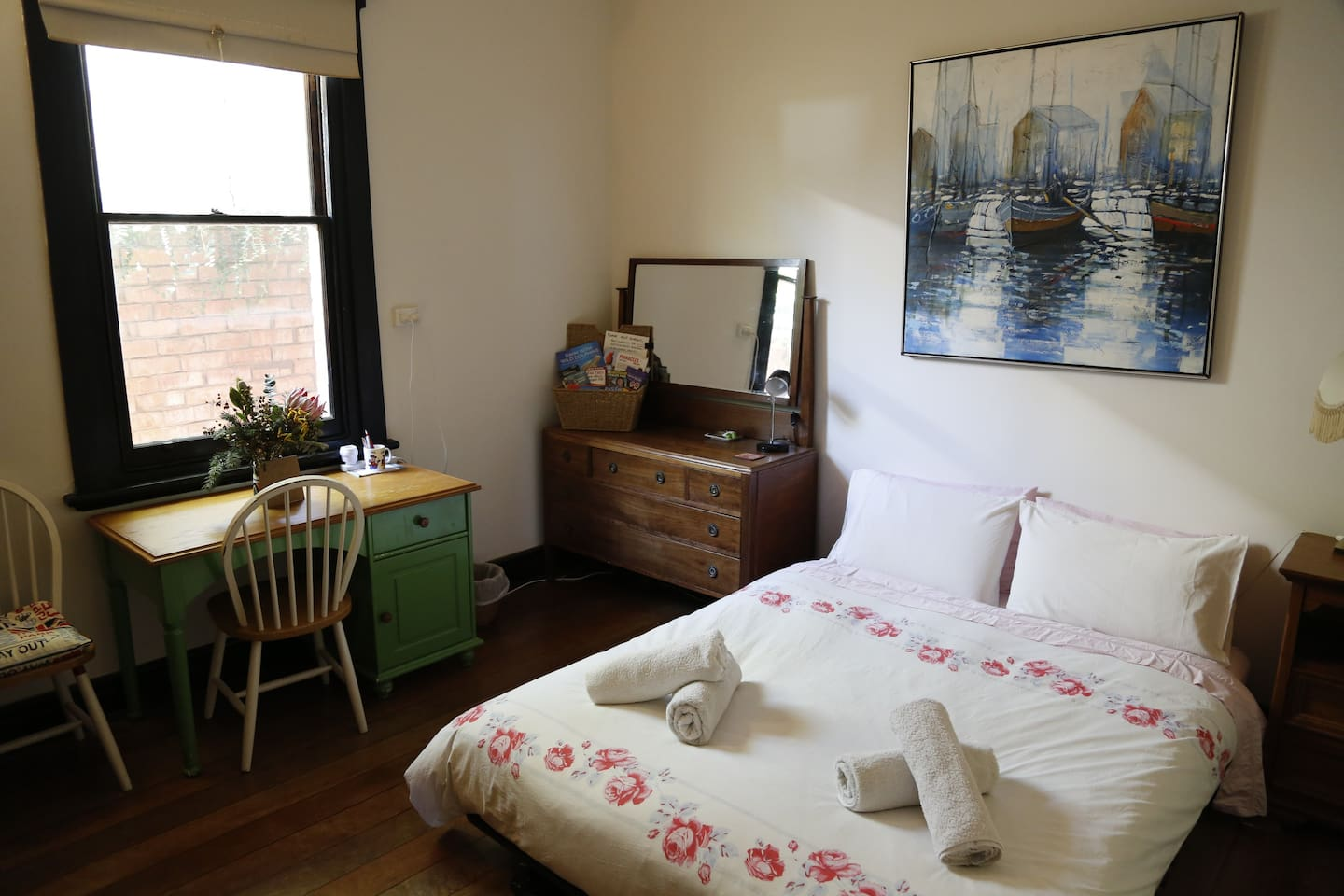 Comfortable queen sized bed in generous sized room with side table, dresser, desk and hanging space