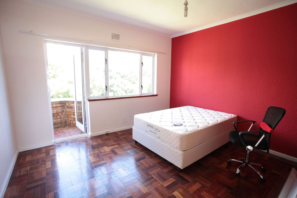 large room with balcony, double bed, fitted wardrobes and desk with wooden floors