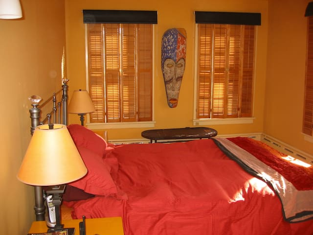 Another view of your room with shuttered windows and roll down darkening shades. There are 4 windows, flooding the room with sunlight during the day. There is also a comfortable chair and a walk-in closet.