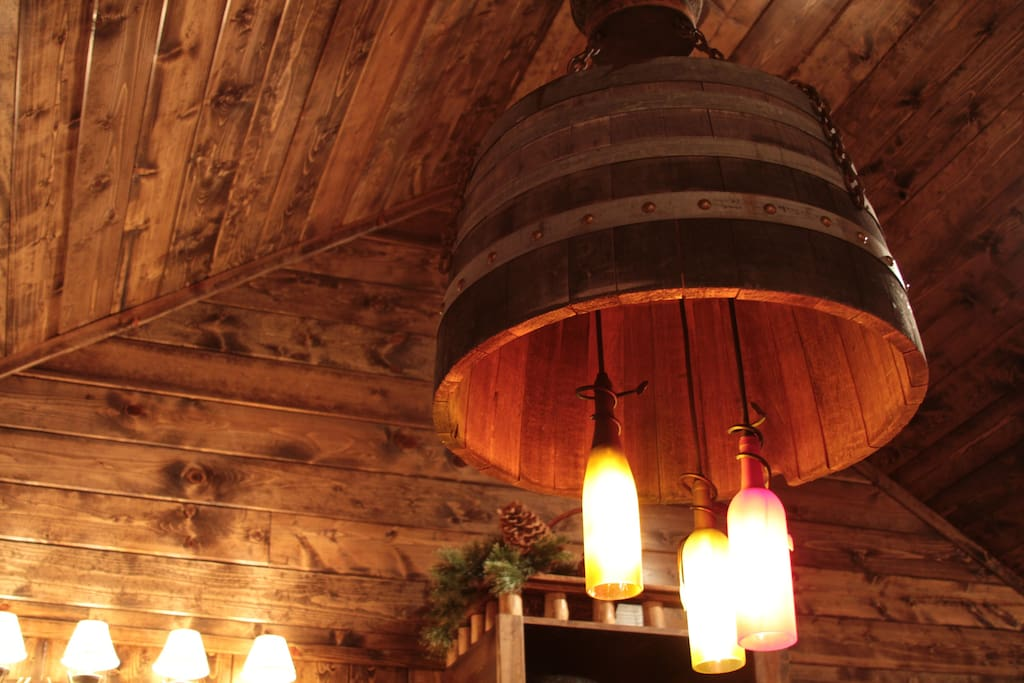 Main chandelier designed with wine bottles and whiskey barrel.
