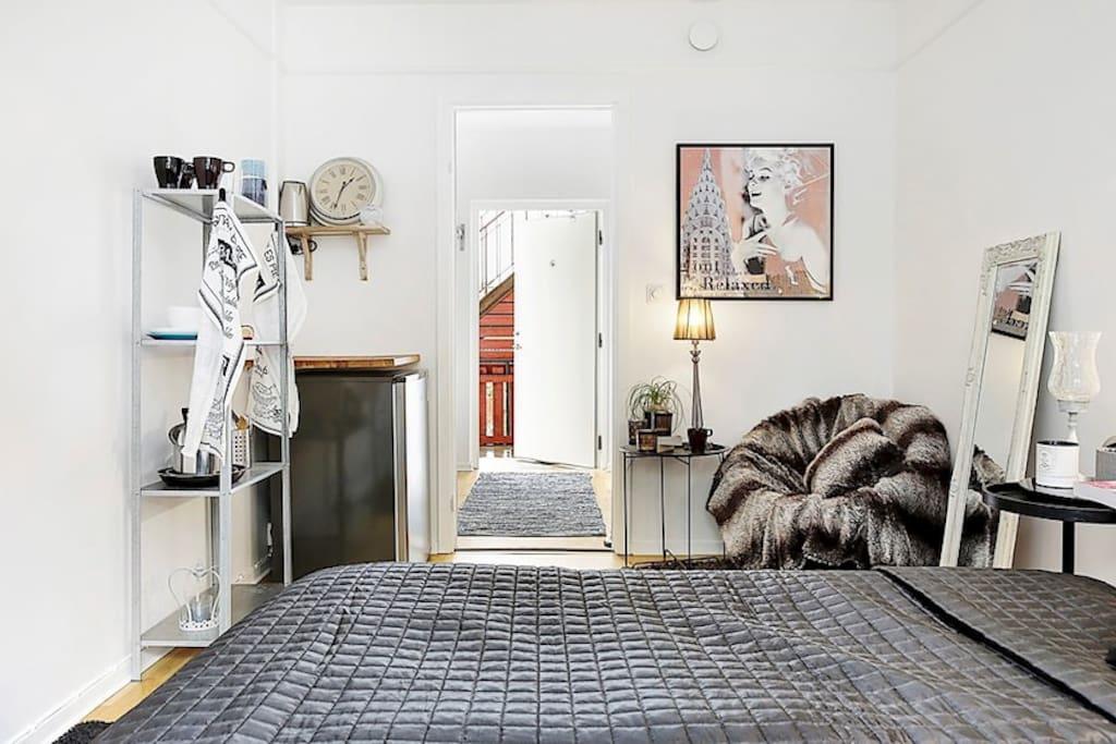 Dubbelsäng med tillhörande påslakan,  täcke och kuddar. Kyl/frys finns tillgänglig. Runt litet matbord med två tillhörande stolar och köksredskap finns tillgängligt.