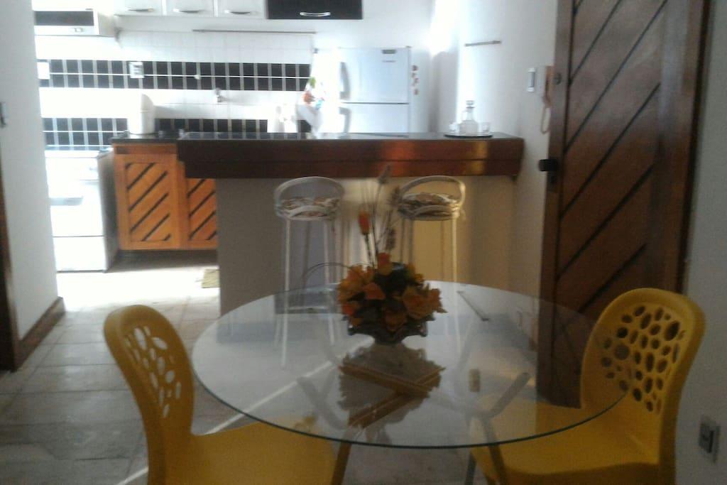 cozinha americana, com geladeira, balcão para pequenas refeições, bancos, fogão e filtro para garrafão de água