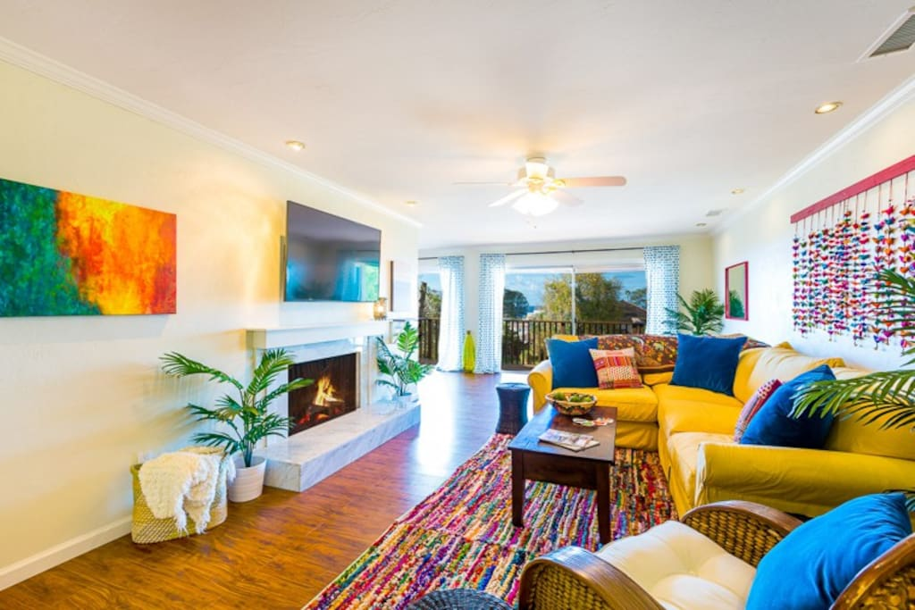 Spacious Living Room has colorful decor, a marble  fireplace and a flat screen TV.