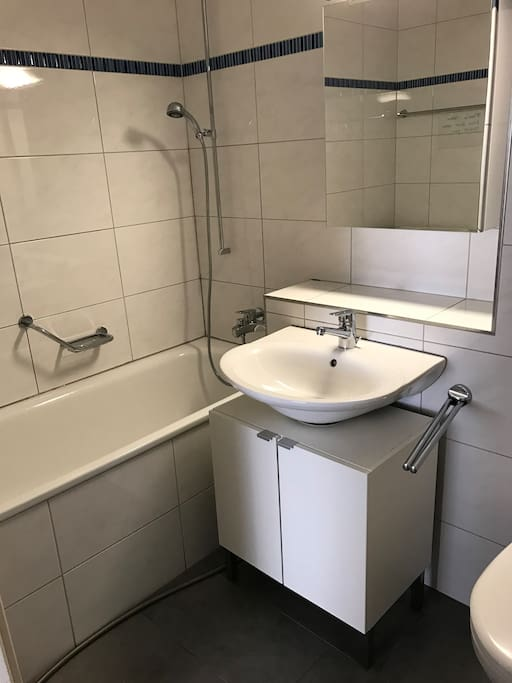 The bathroom has a bathtub and a washingmachine.