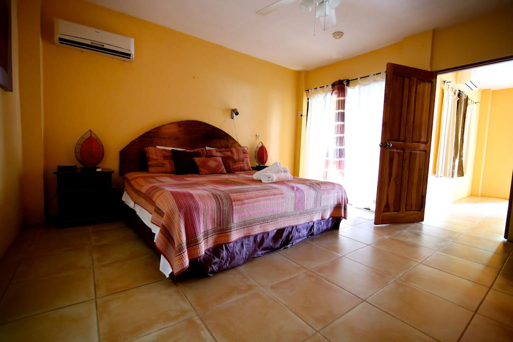Back bedroom with private entrance, king size bed, A/C, TV, fan, comfortable  bed.