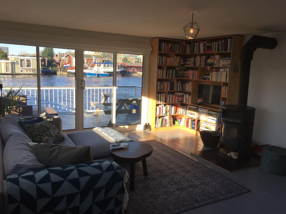 Living room, open kitchen, view on the canal and a fireplace