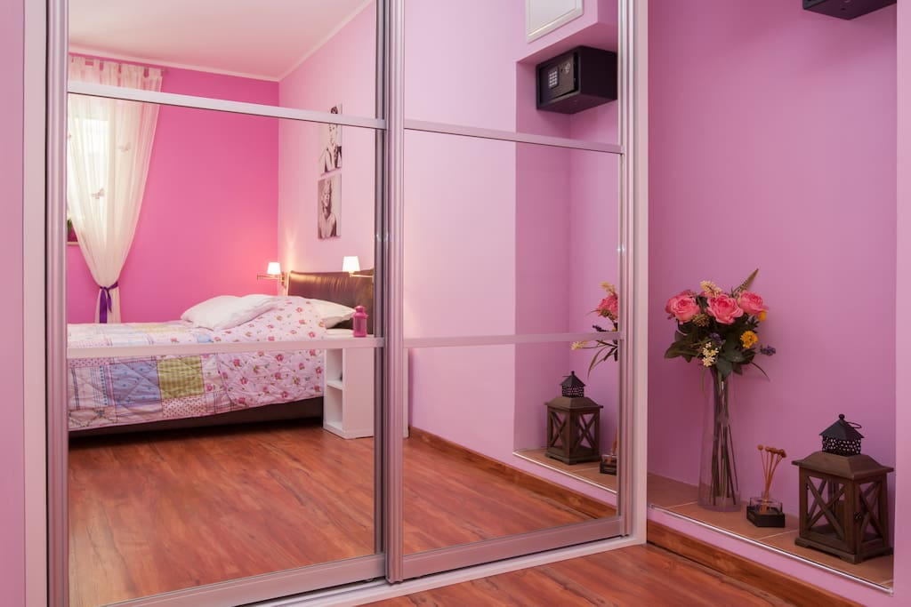 Wardrobe behind mirror in bedroom