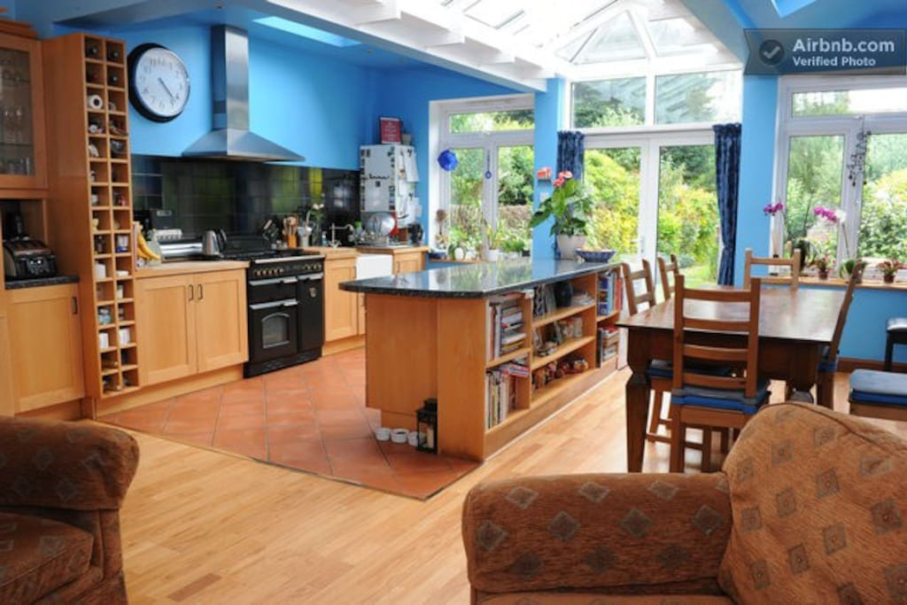 Large kitchen/dining morning room looking out to mature English garden of Edwardian house