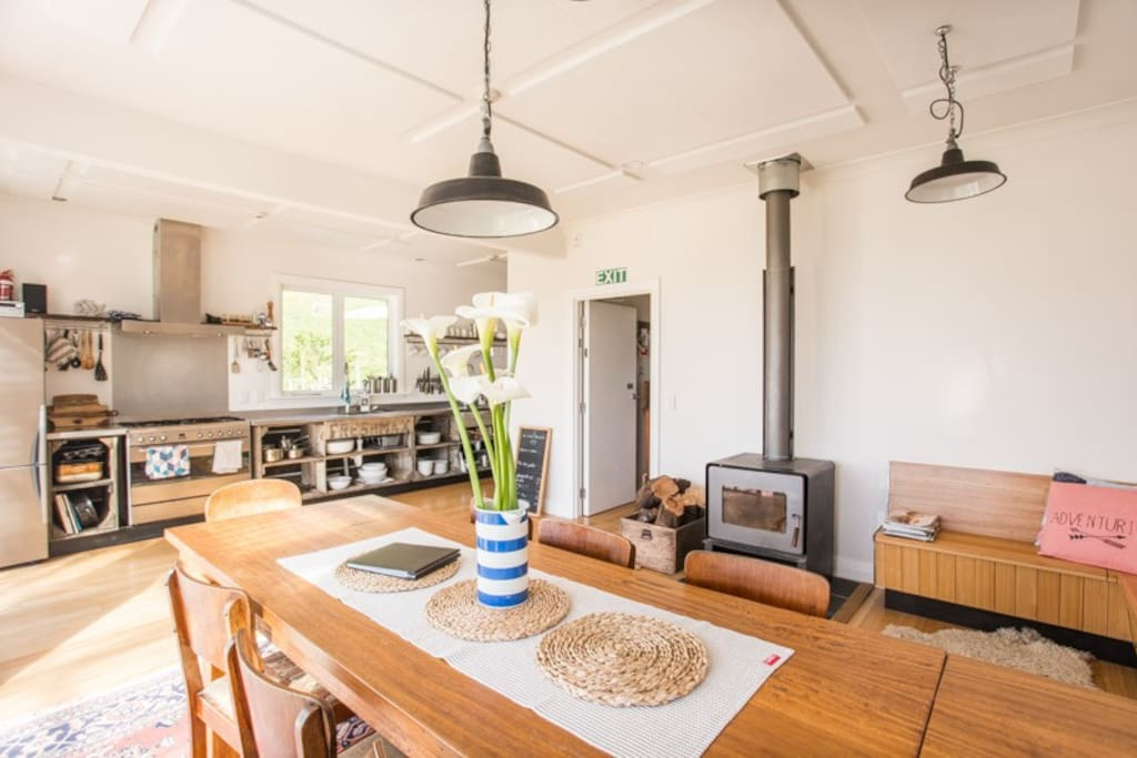 The open plan dining/kitchen area. Farmhouse dining table, with cosy log fire, and doors opening onto sunny verandah. Very flexible open-plan space.  We can include a second dining table for larger groups,  if required.