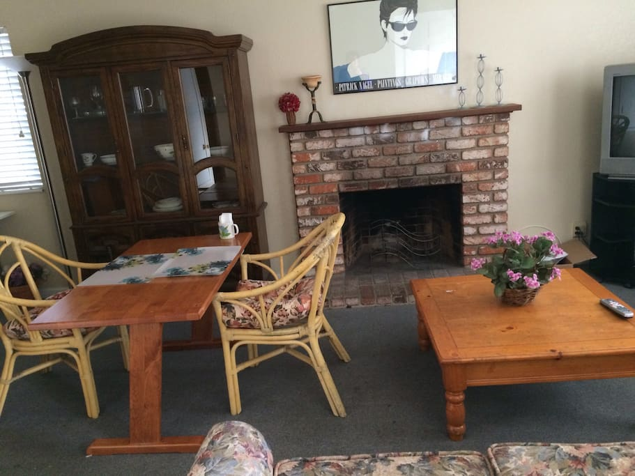 Large living/dining area with fireplace, sofa,TV, reading area, desk.