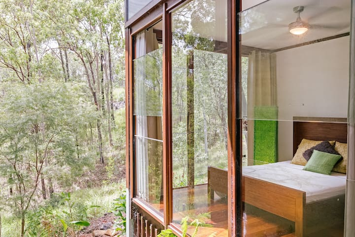 A luxury treehouse. Queen bed guest room with floor to ceiling windows.