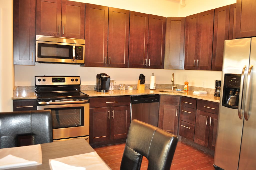 Kitchen has granite counter tops, stainless steel appliances, and lots of storage.