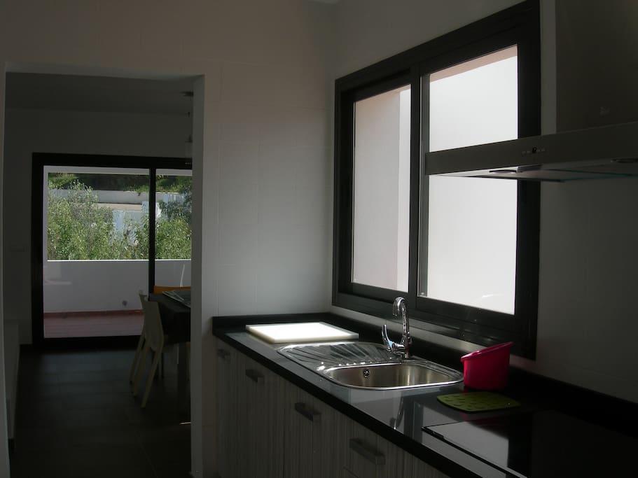 Cuisine ouvrant sur la salle à manger et une terrasse couverte côté Sud