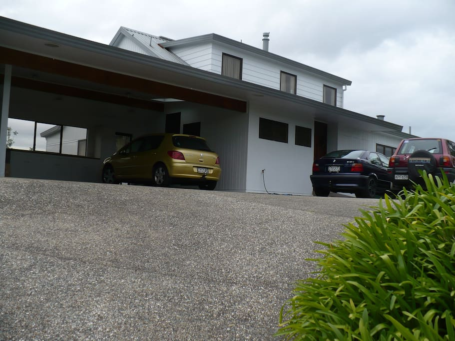 View from the road of house with double carport and outdoor parking.
