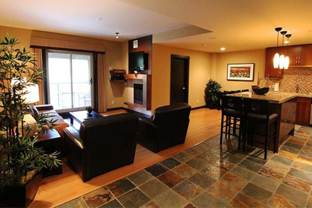 Stunning open concept living area with a welcoming fireplace to warm up with