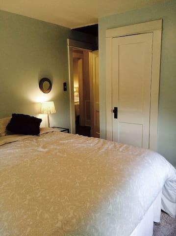 Queen bed in Bedroom 1 with closet, dresser and flat screen TV