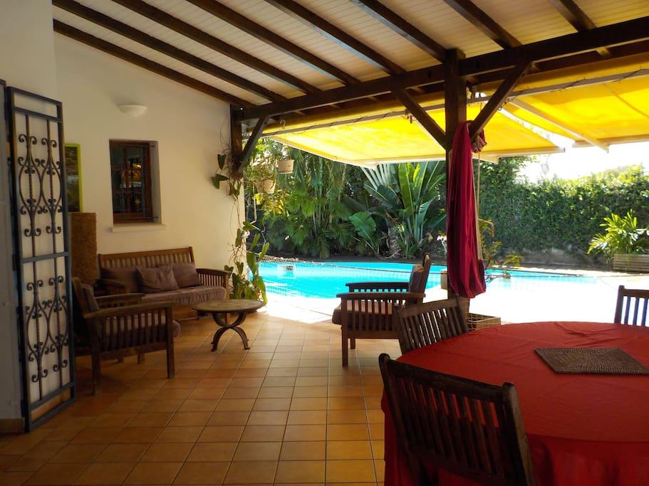 Terrasse couverte accès piscine et deck, coin repas et salon