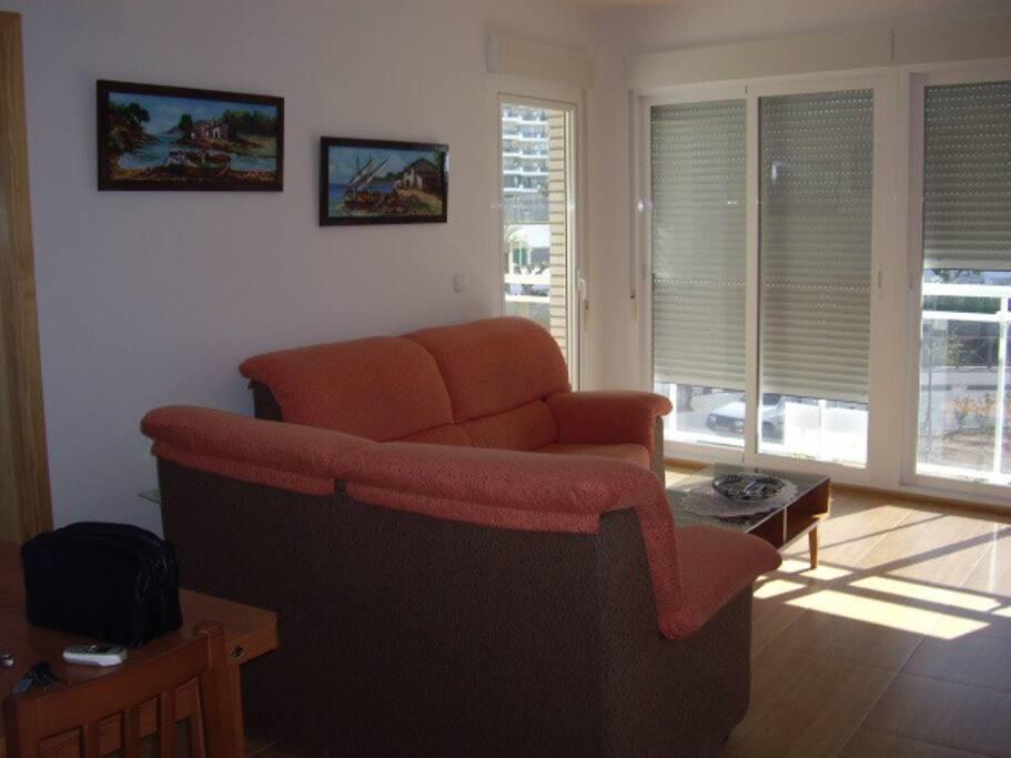 Salón con ventanales y pequeña terraza. Vistas al mar y al castillo