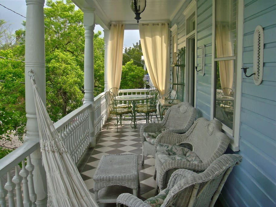 A private front porch spans the front of the home and overlooks the gardens of the mansion across the street.