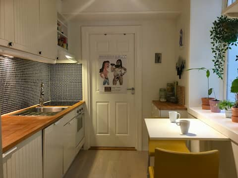 A fully equipped kitchen with a table for two.
