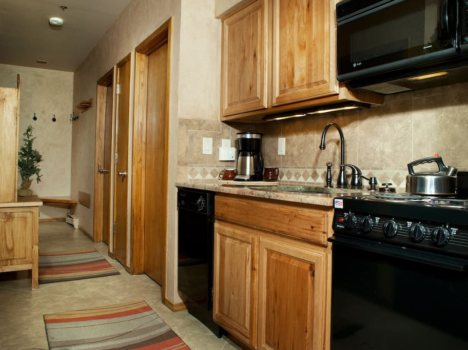 The fully-equipped kitchen features a natural wood finish