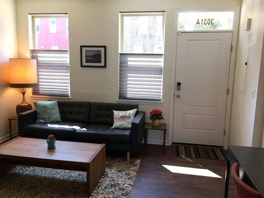 The front room has a big, comfy couch and lots of natural light.
