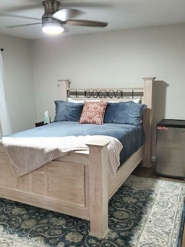 Guest Bedroom with queen bed and mini-fridge.