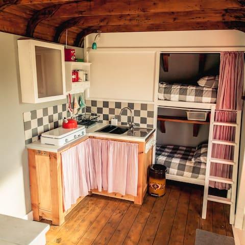 De keuken is compleet ingericht, inclusief een koelkastje en warm water